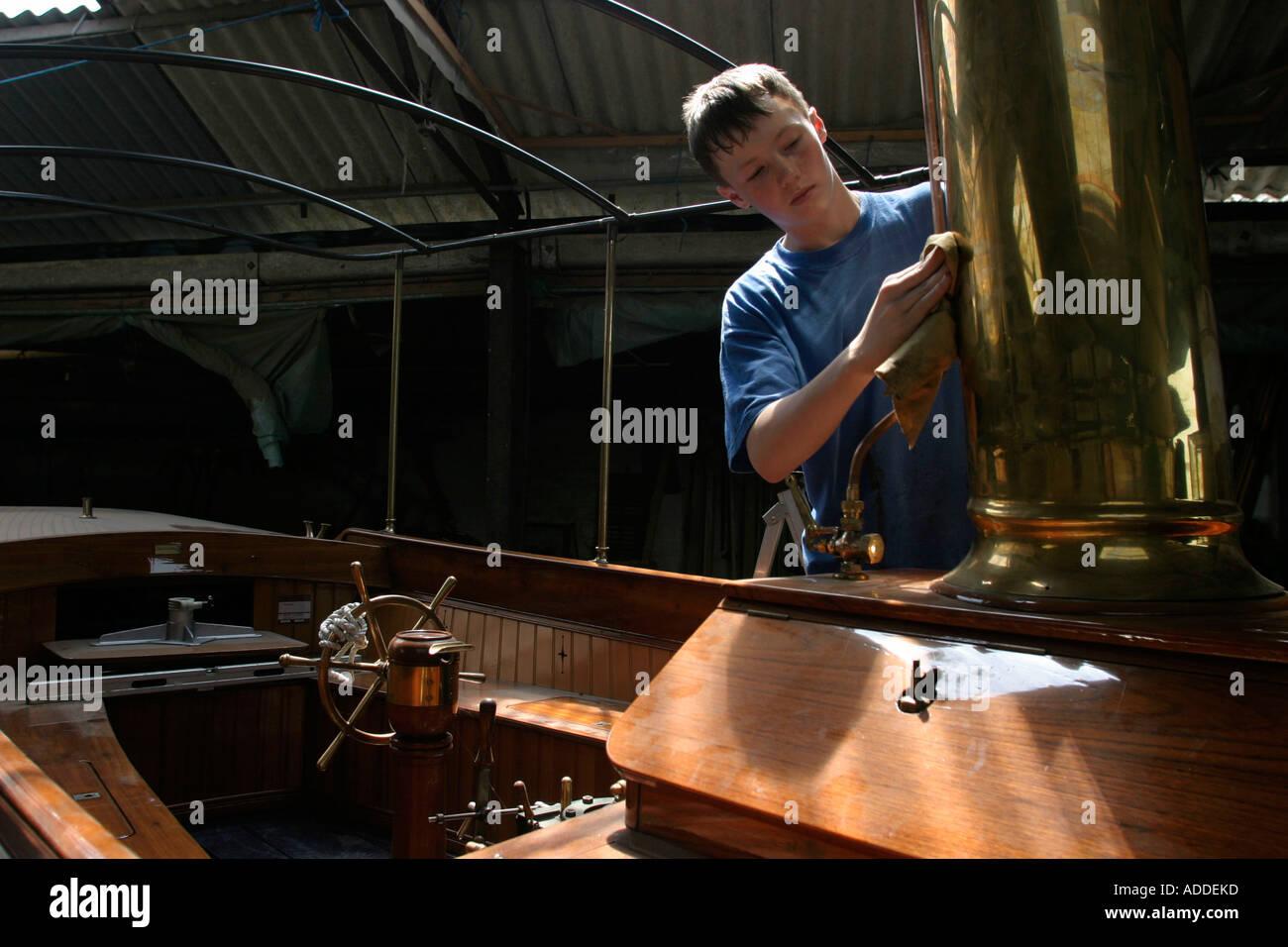 Hambleden Jake, 16, polishes the funnel of a Thames steam boat in the Henwood and Ding boatyard on the Hambleden estate - Stock Image
