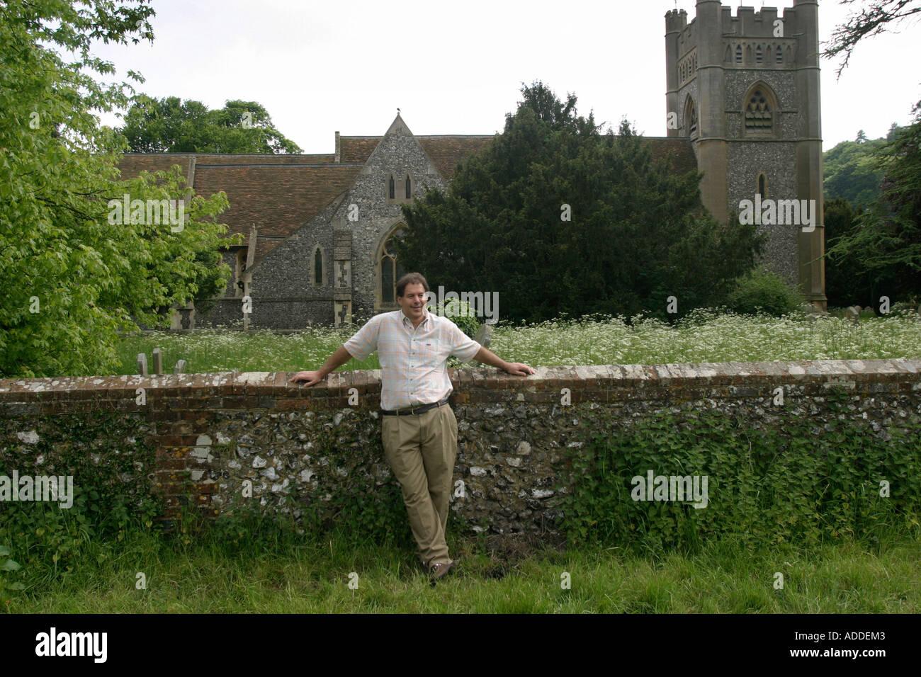 Hambleden:  Henry Smith, 48,  heir to Viscount Hambleden, beside the village church yard. - Stock Image