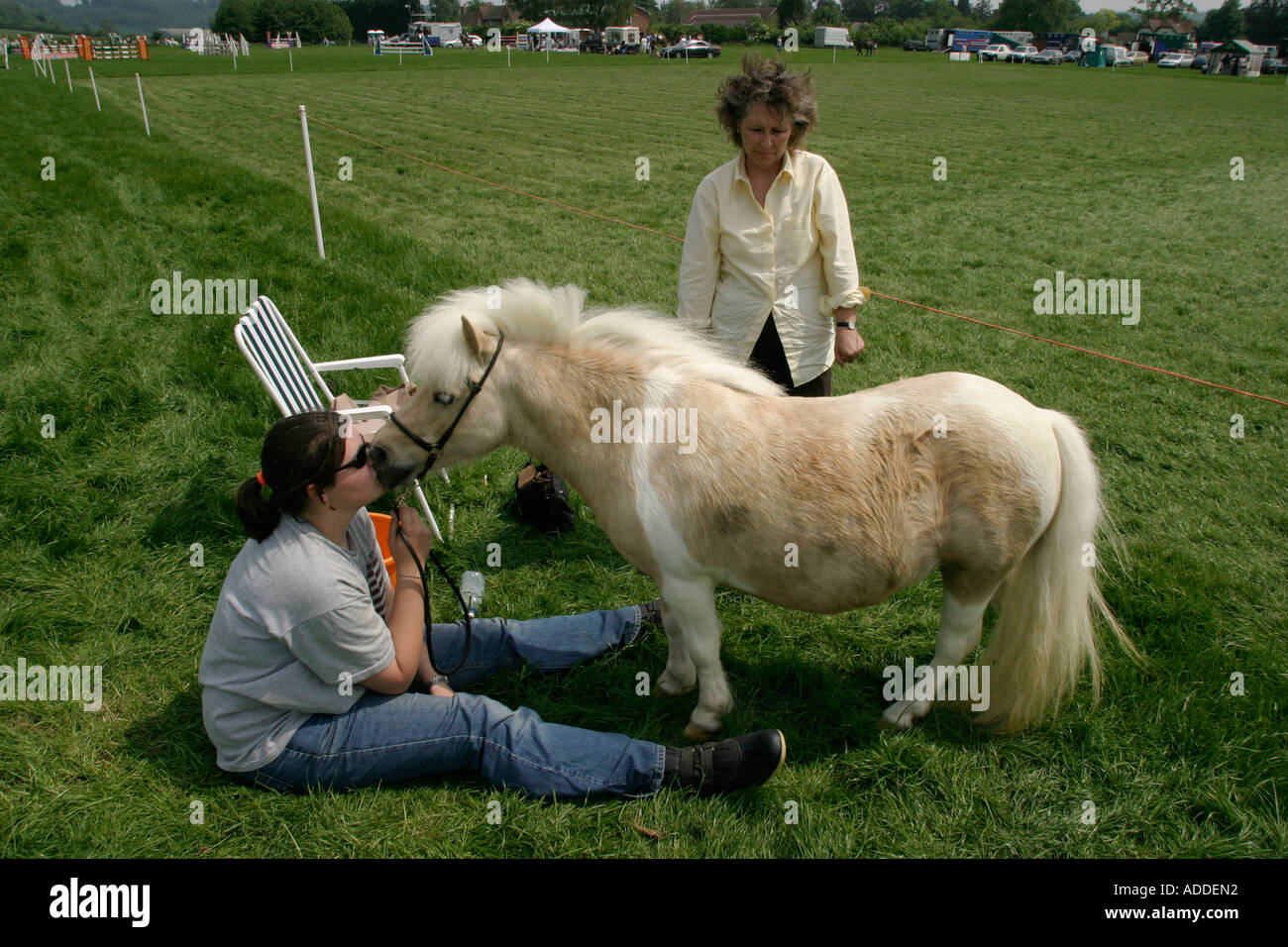 A girl kisses her miniture Shetland pony at the South Oxfordshire Riding Club's Open Show - Stock Image