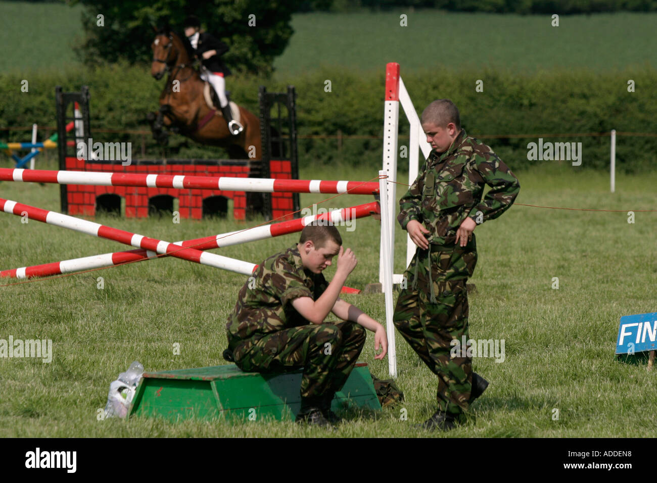 Army cadets help at the South Oxfordshire Riding Club's Open Show on the Hambleden Estate as rider jumps a fence. - Stock Image