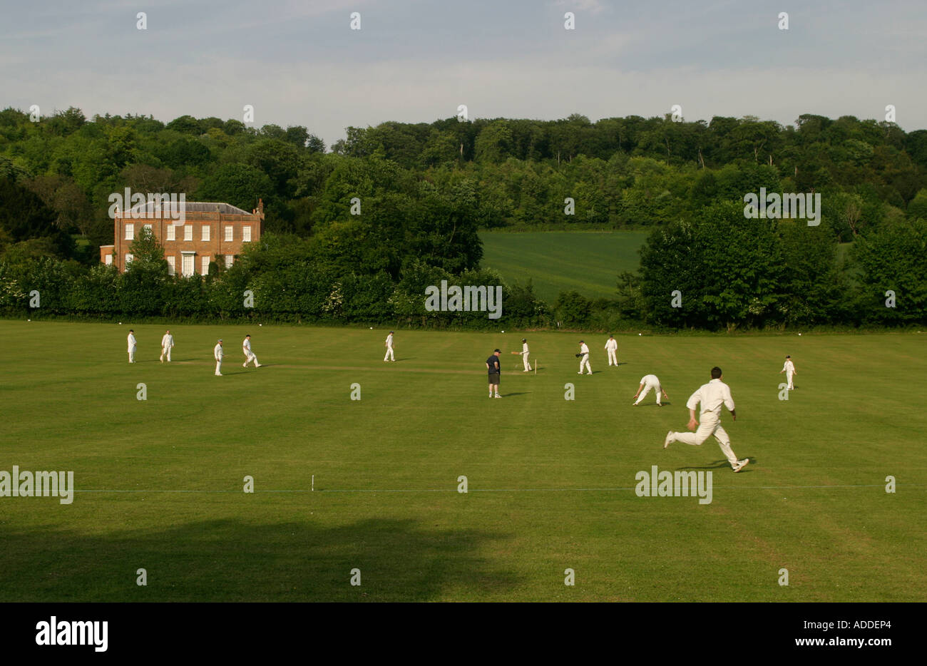 Fielder runs to stop the ball during a cricket match on Hambleden village playing fields, Hambleden. - Stock Image