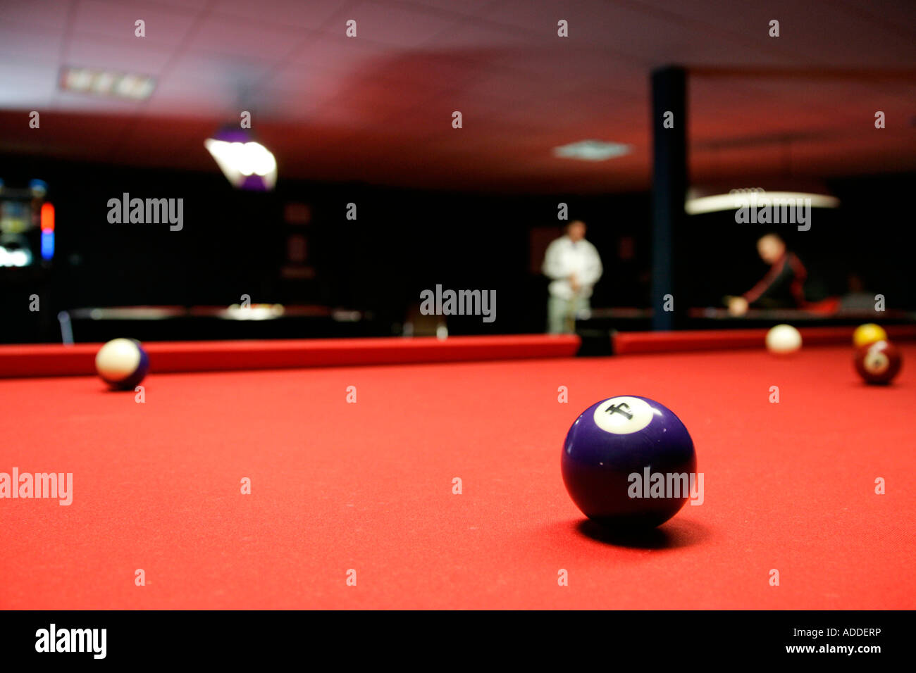 Purple 4 Ball Sitting On A Red Cloth Pool Table In A Pool Room With People