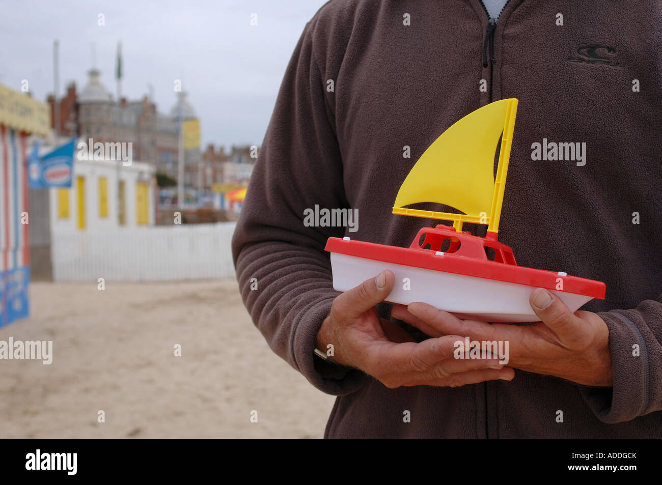 A man holding a toy sailing boat on the beach in Weymouth, Dorset, UK, a venue for the sailing events of the 2012 - Stock Image