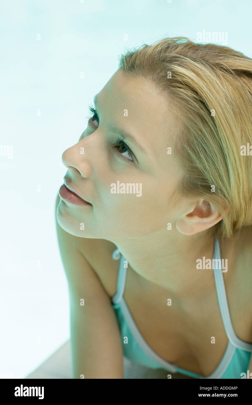 Woman lying by pool, looking up, close-up portrait - Stock Image