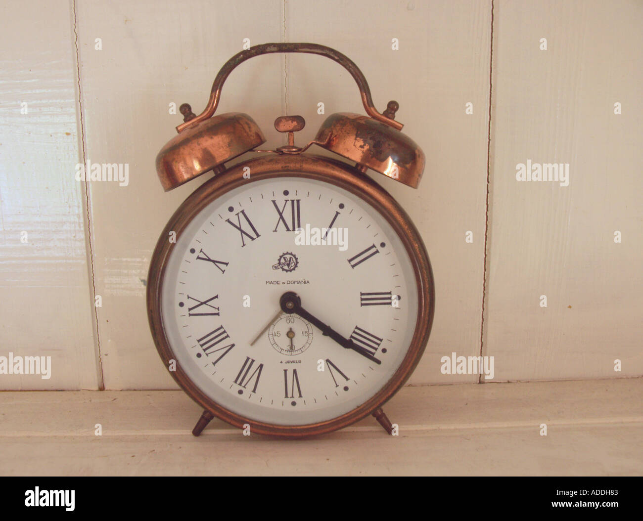 Old brass clock face with hands and roman numerals - Stock Image