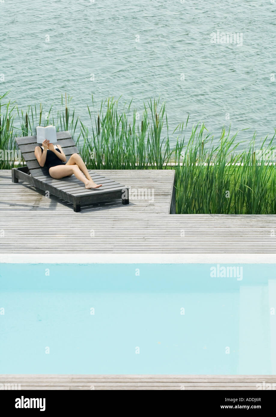 Young woman lying on lounge chair, reading - Stock Image