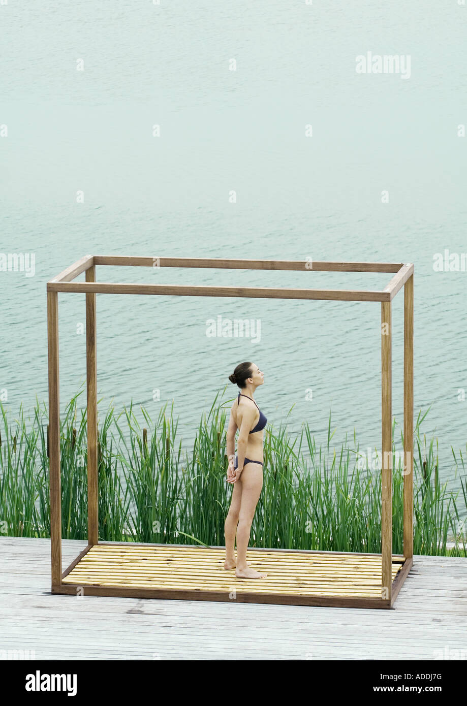 Young woman standing inside square structure, next to body of water - Stock Image