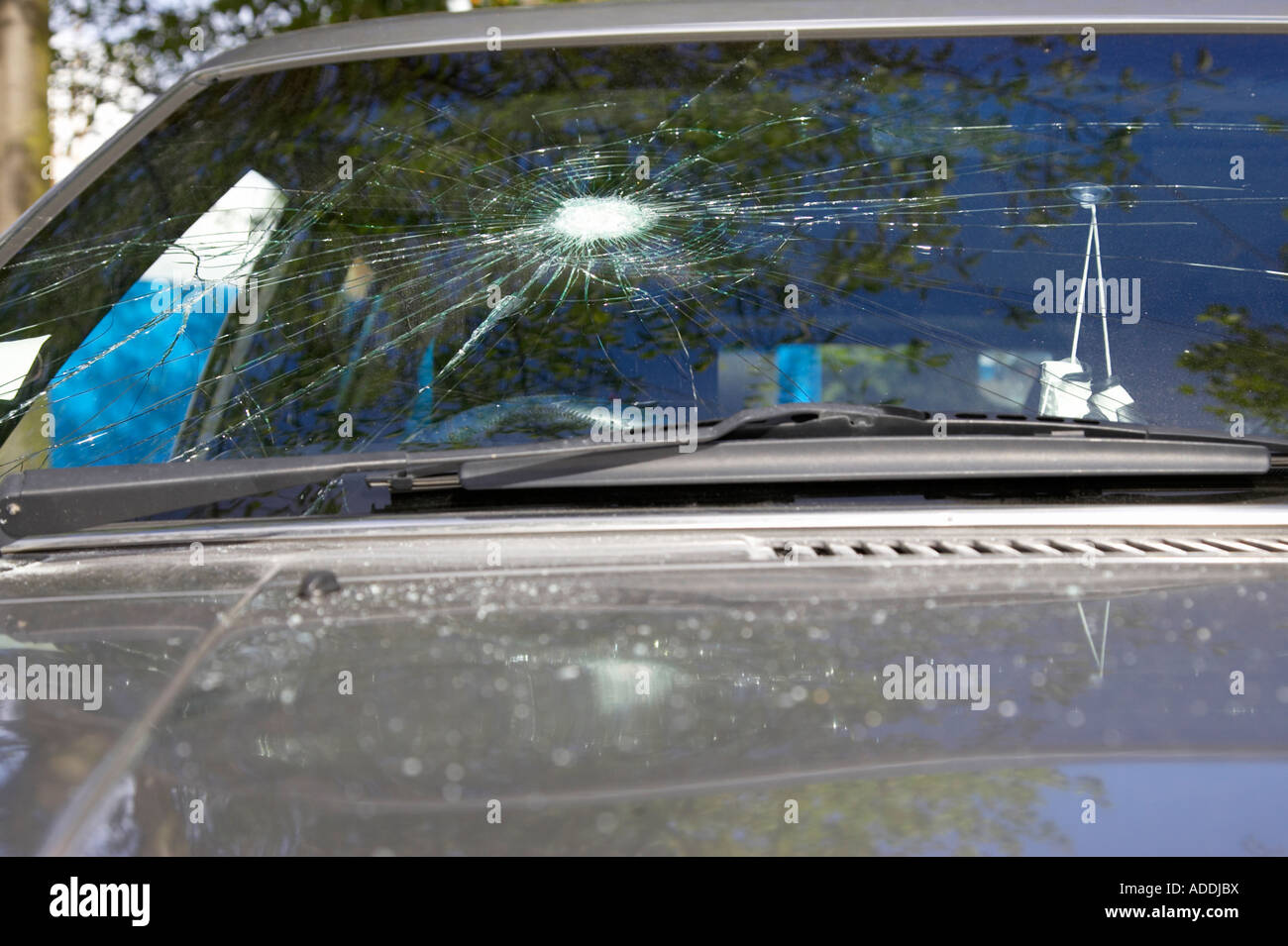 smashed cracked car windscreen caused by vandals with glass fragments on the bonnet - Stock Image