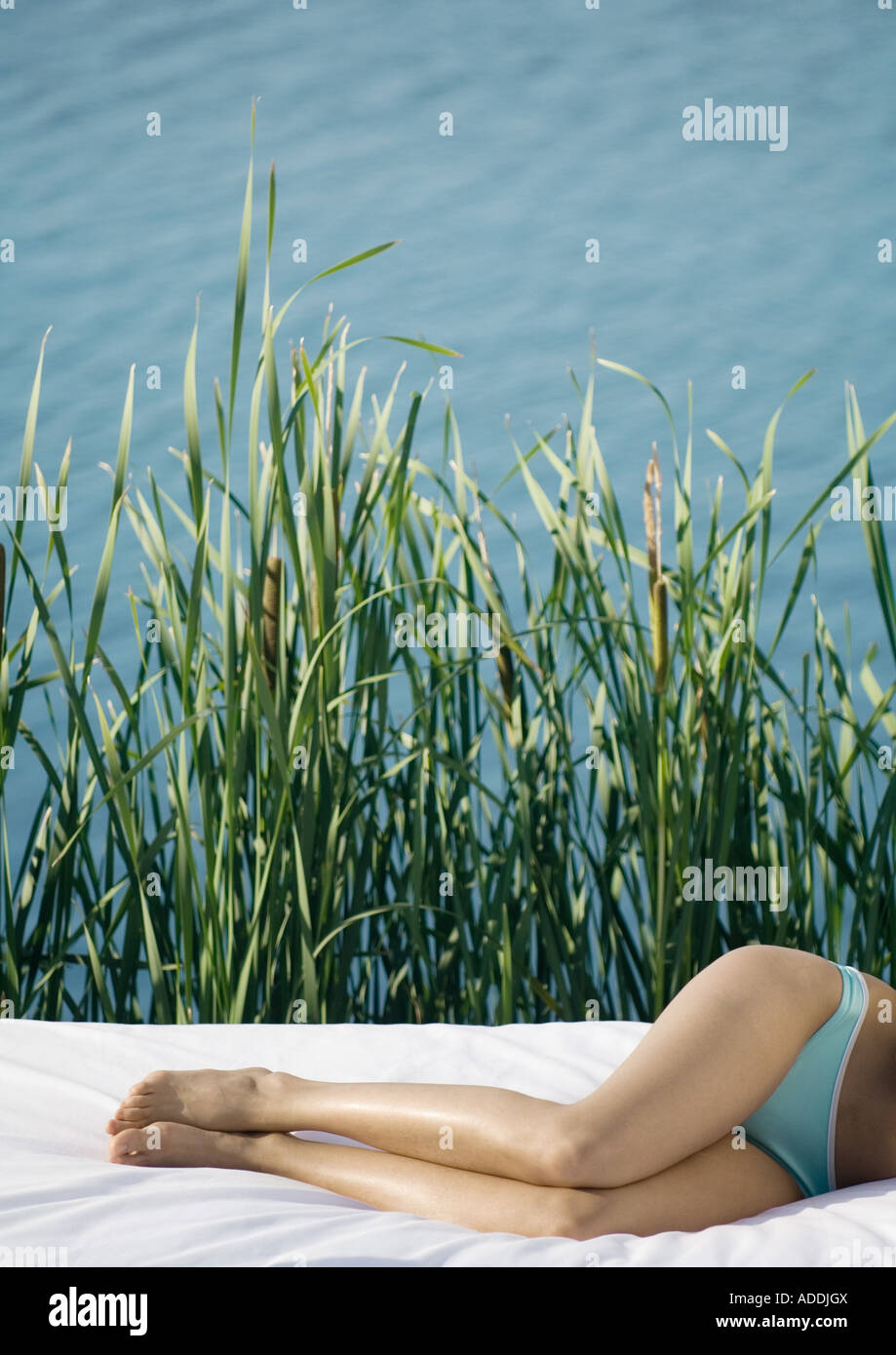 Woman lying on side, waist down, water and reeds in background - Stock Image