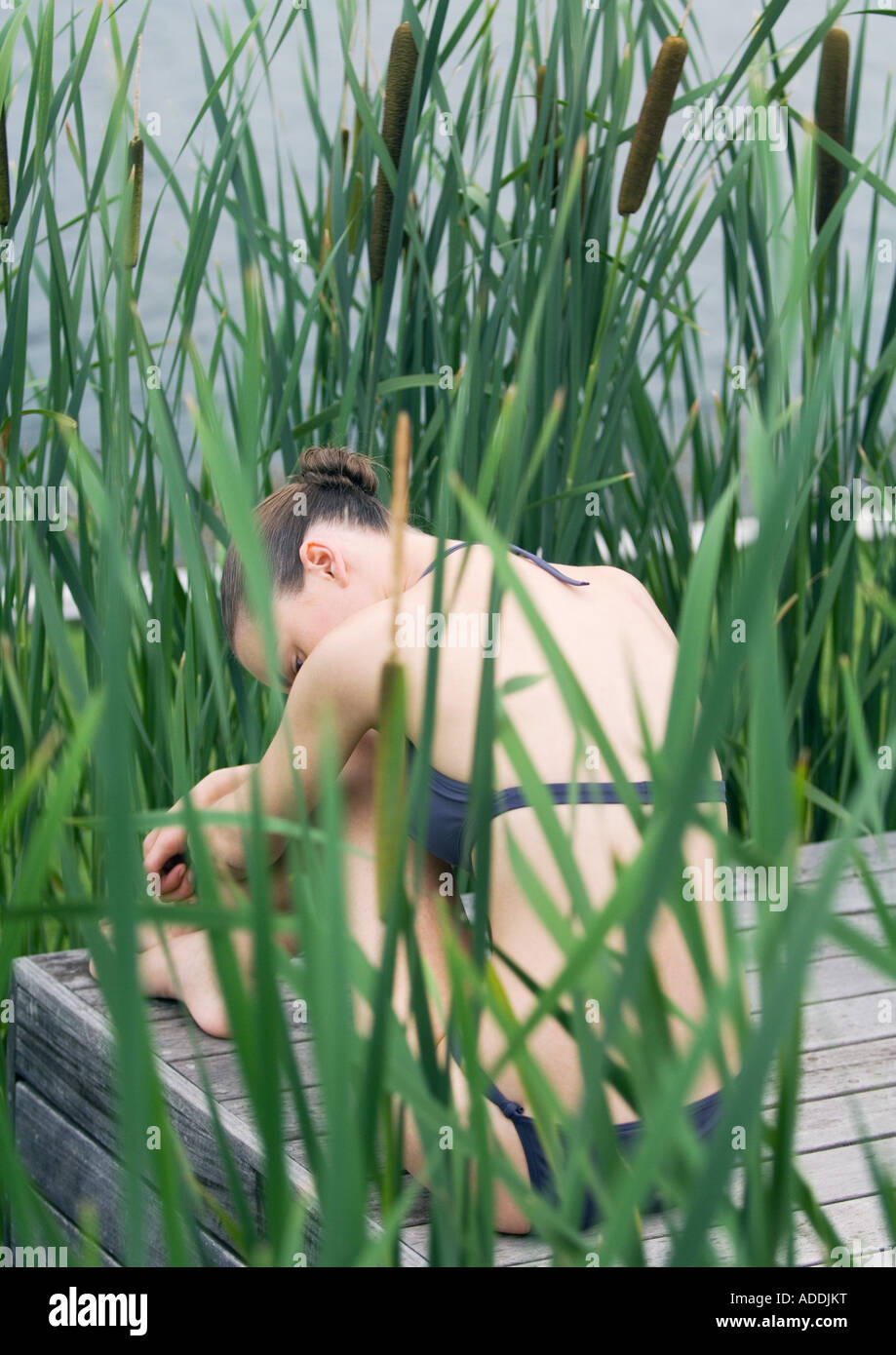 Young woman sitting on deck in bikini with head on knees, surrounded by reeds, rear view - Stock Image