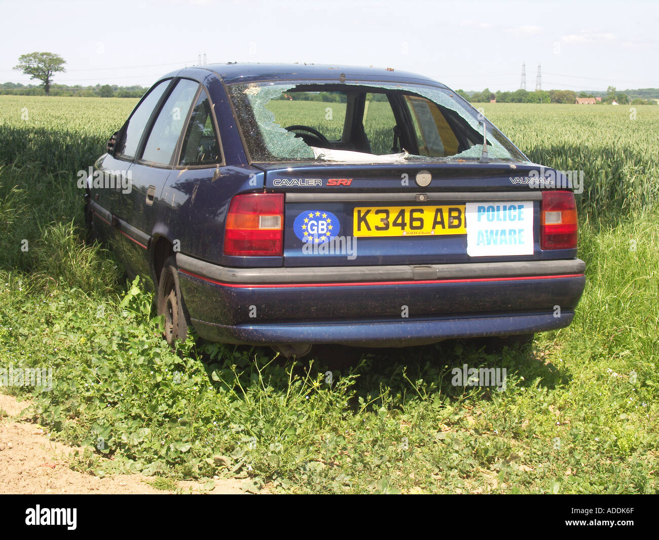 Abandoned car with smashed rear window in a field with Police Aware sticker - Stock Image