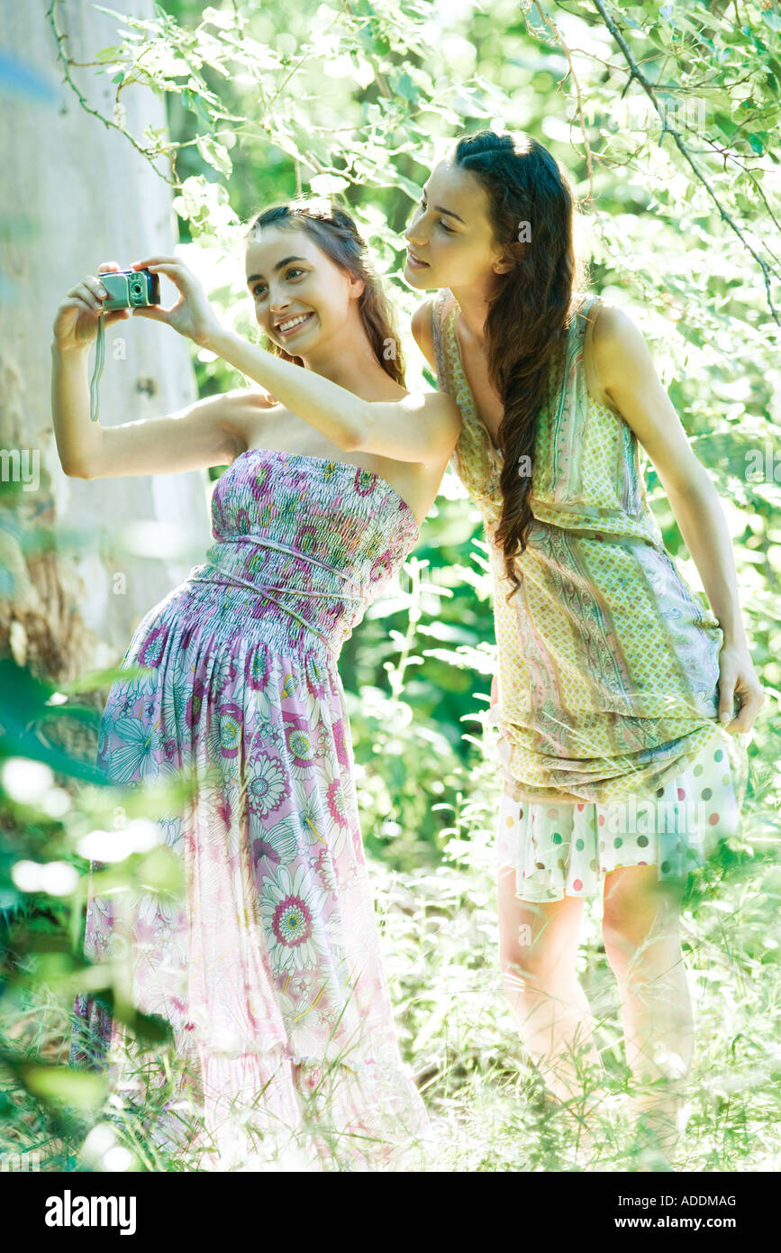 Two young women wearing sun dresses, standing in forest, taking photo with digital camera - Stock Image