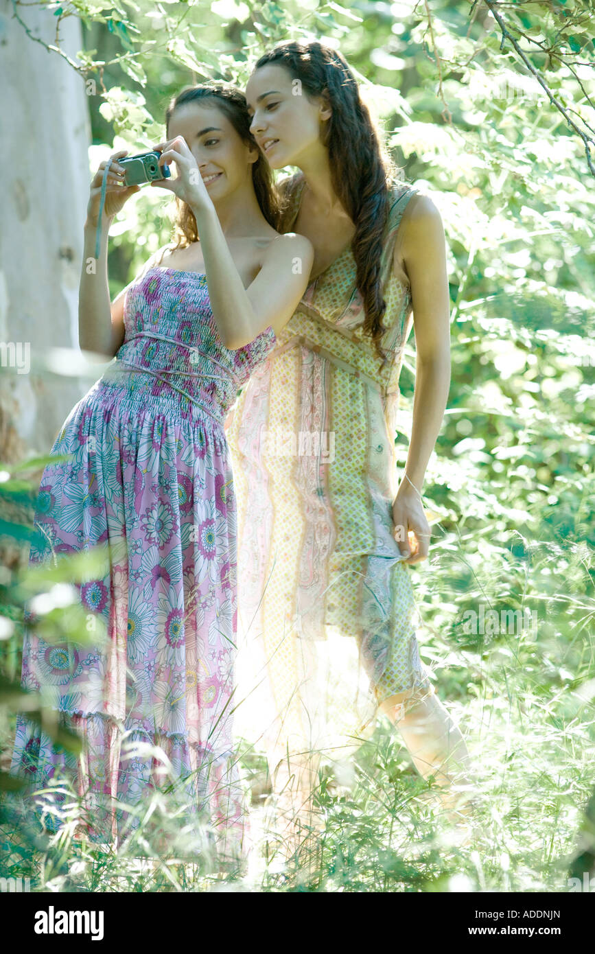 Two young women wearing sun dresses, standing in forest, looking at digital camera - Stock Image