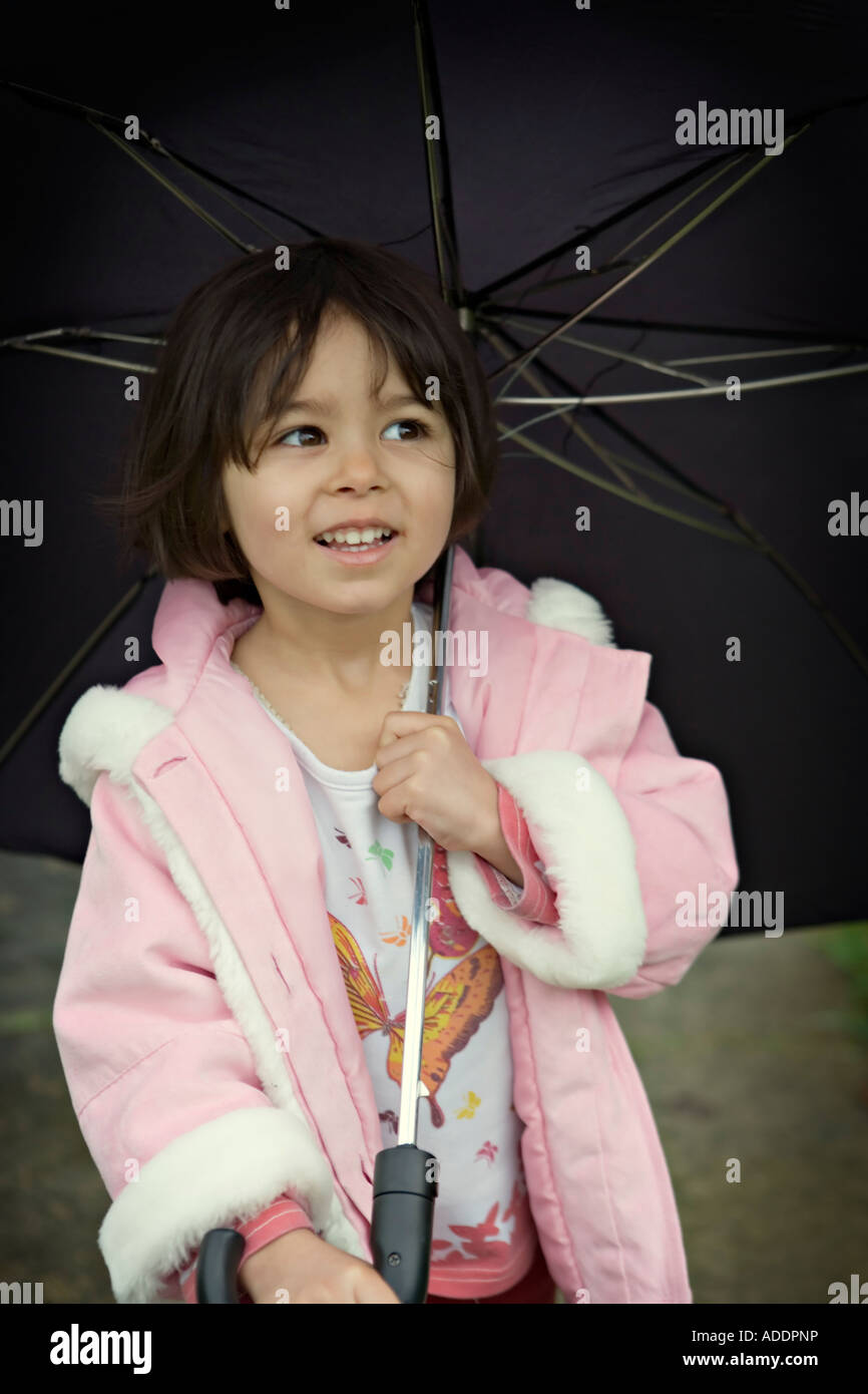 Girl in pink coat with umbrella - Stock Image