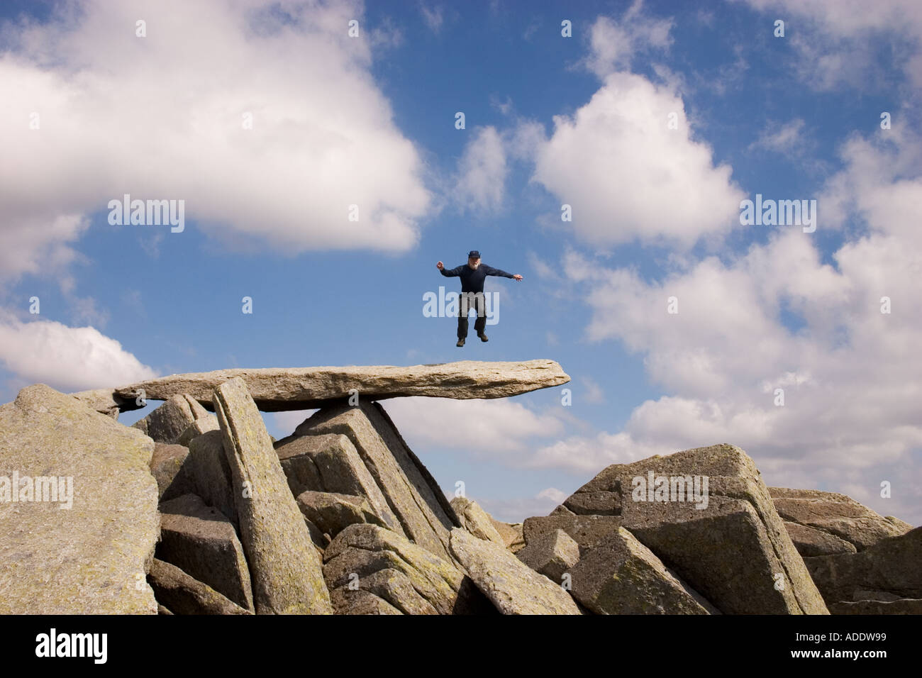 Pat Bennett in mid air above The Cantilever a wellknown feature near the summit of Glyder Fach Snowdonia - Stock Image