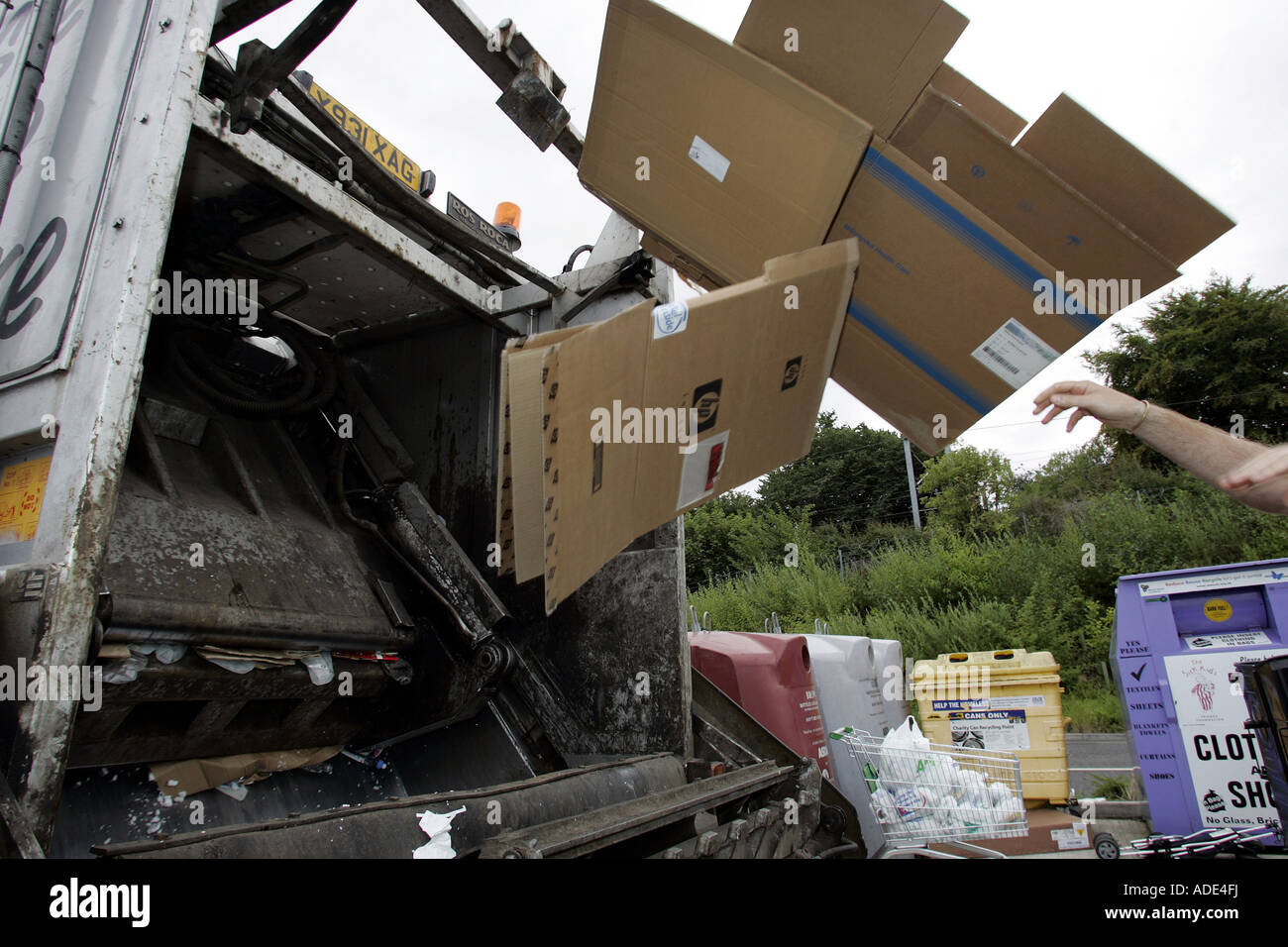 CARDBOARD BOXES BEING THROWN INTO THE BACK OF A REFUSE LORRY. - Stock Image