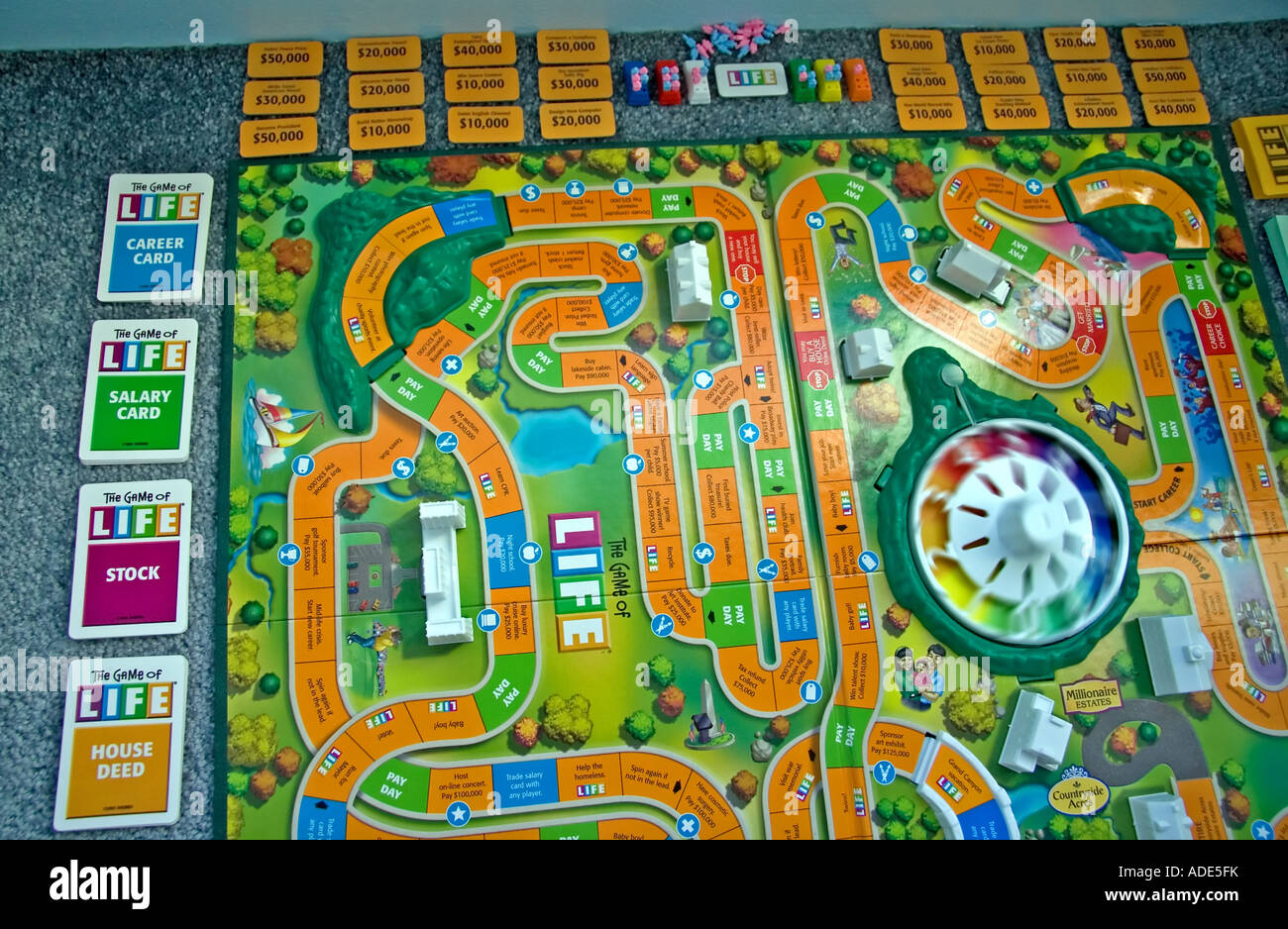 """The Game of Life"" by Milton Bradley. The gameboard & all its' pieces spread out. Stock Photo"