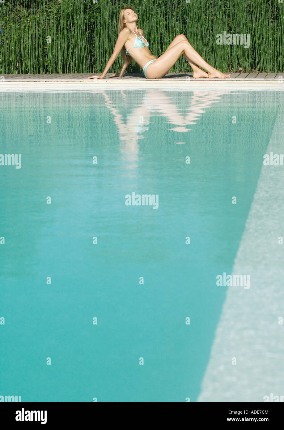 Young woman sitting by edge of pool with knees up, full length - Stock Image