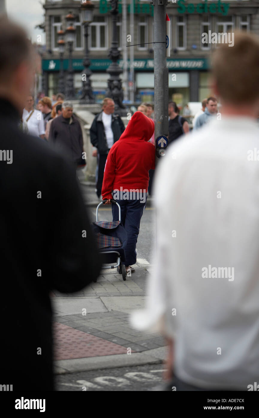 woman in red hoodie and blue trousers pulling a shopping wheeled trolley standing leaning against pedestrian crossing - Stock Image