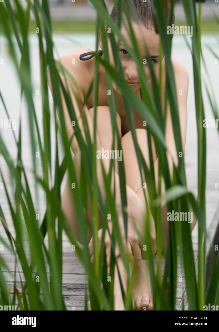 Young woman sitting on deck in swimsuit, reeds in foreground, looking at camera - Stock Image