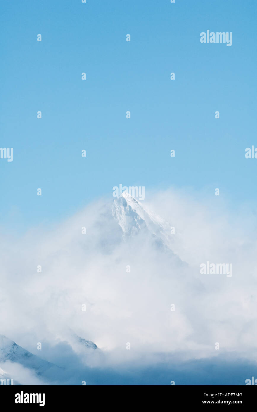 Snow-capped mountain surrounded by clouds - Stock Image