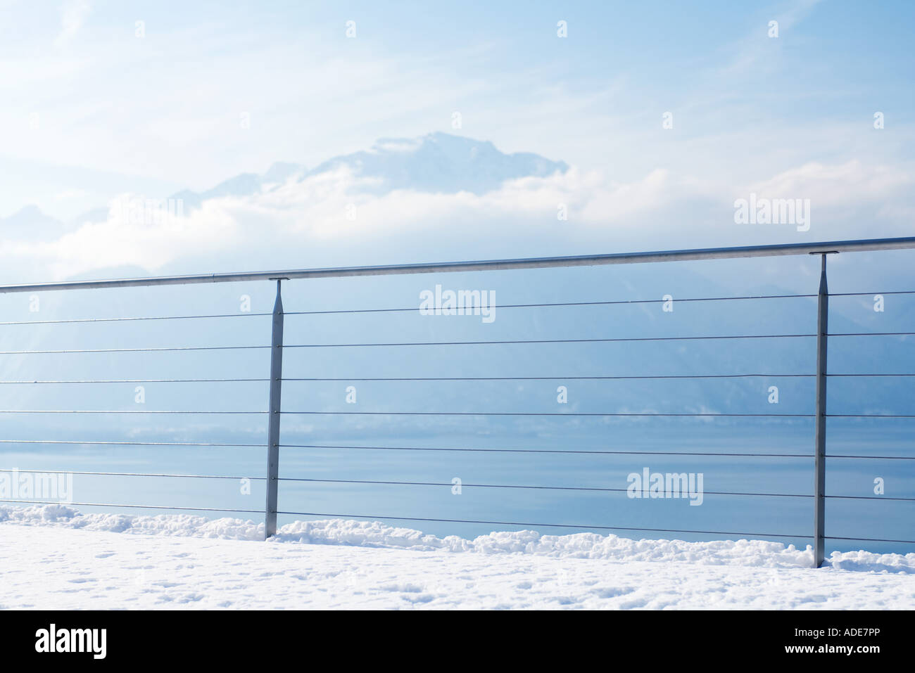 Snow-covered lookout area with lake and mountains - Stock Image