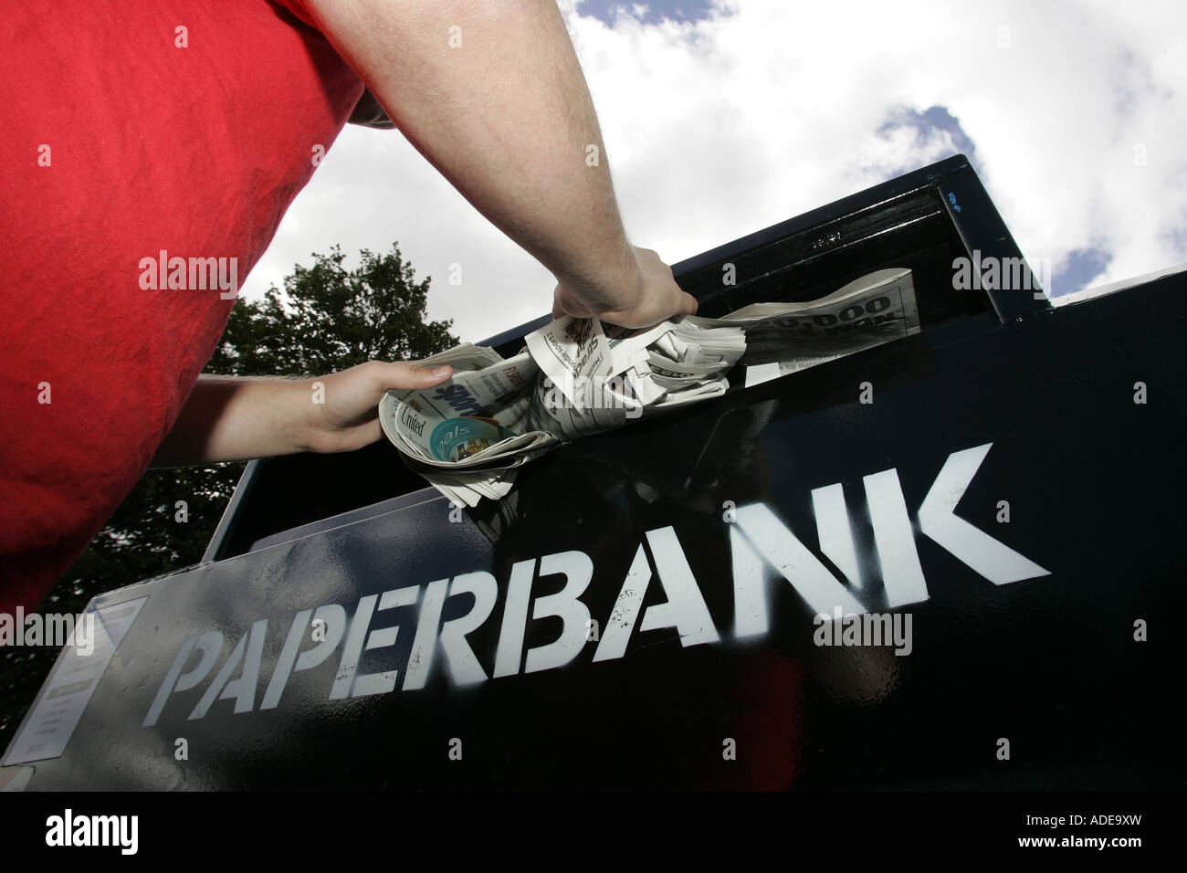 A YOUNG MAN RECYCLES NEWSPAPERS AND MAGAZINES AT A PAPERBANK. - Stock Image