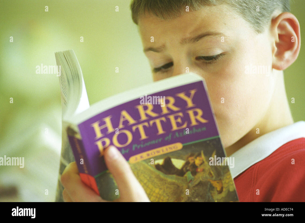 A young reader with a Harry Potter book Harry Potter and the Prisoner of Azkaban in a book shop in Birmingham UK - Stock Image
