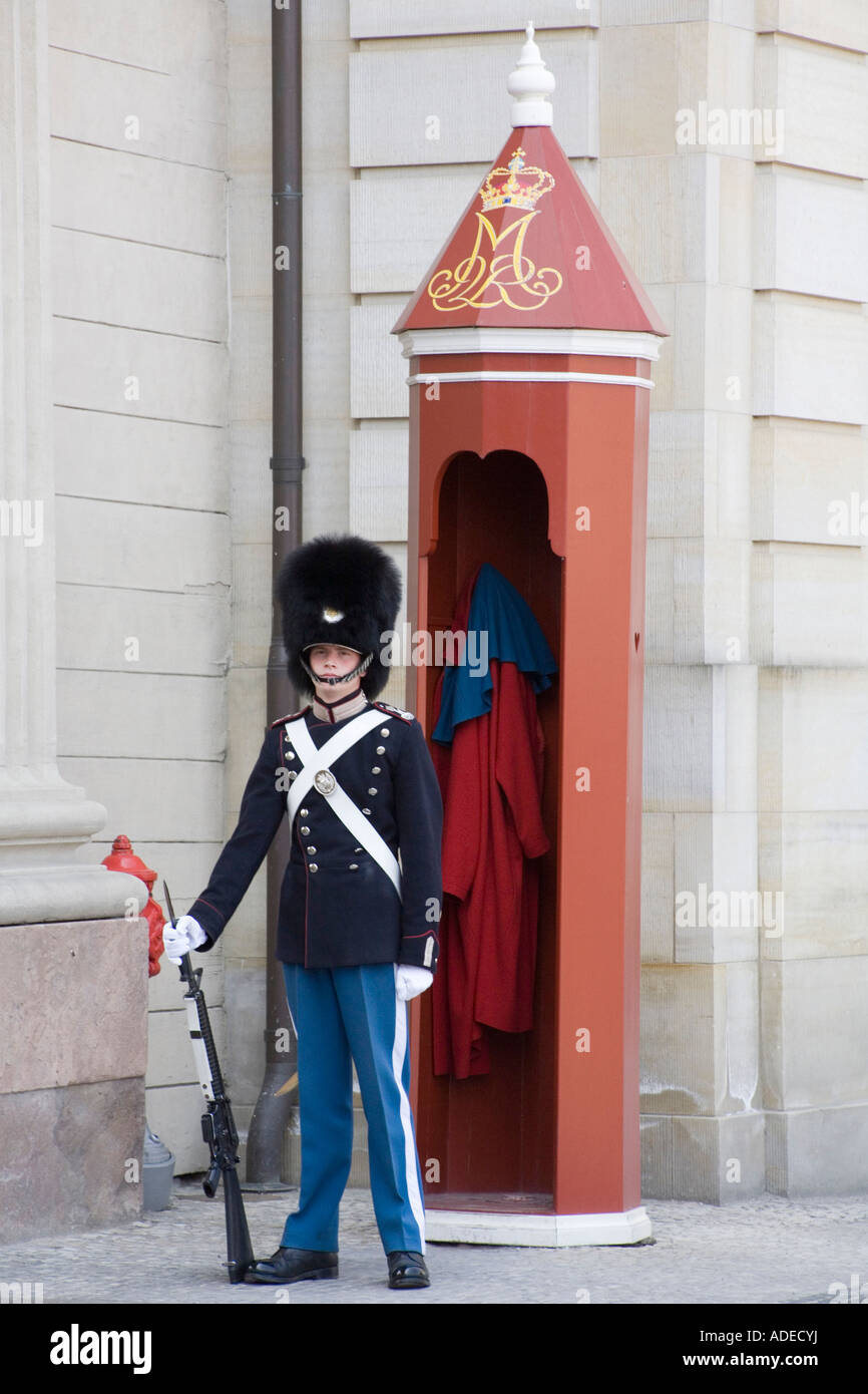 A Danish royal life guard stands outside Amalienborg Royal Palace, Copenhagen. - Stock Image