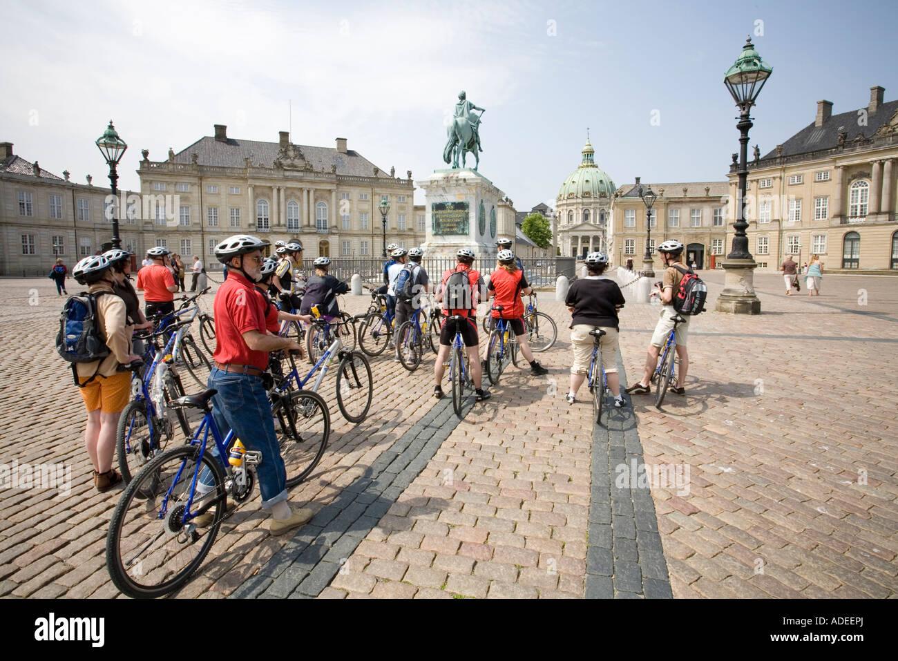 Cyclists on a sightseeing tour of Copenhagen visit Amalienborg Palace - Stock Image