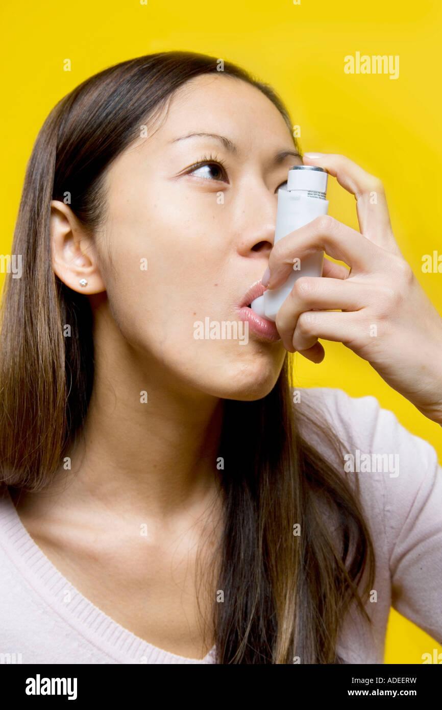 Asthmatic woman using bronchial dialator or puffer. - Stock Image