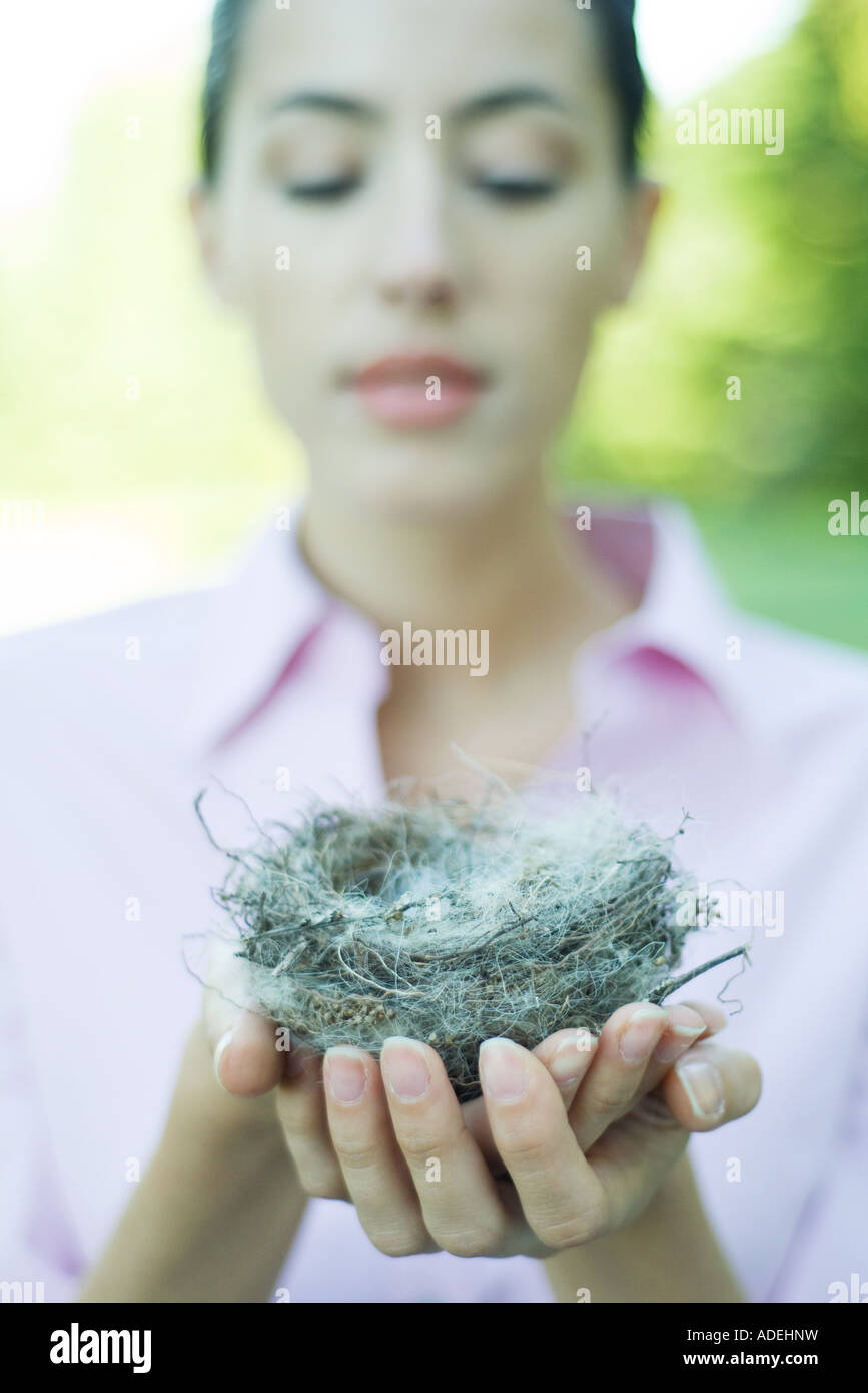 Woman holding bird's nest in palm of hand - Stock Image