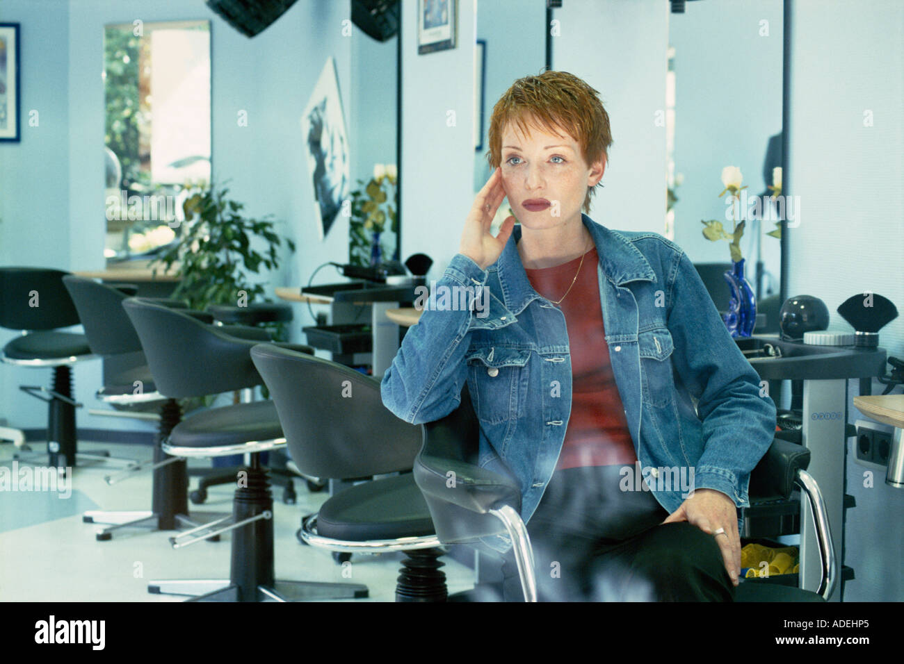 Woman sitting in hair salon. - Stock Image