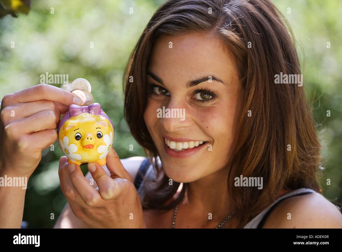 Young woman puts money into a piggy bank © Peter Schatz/Alamy - Stock Image