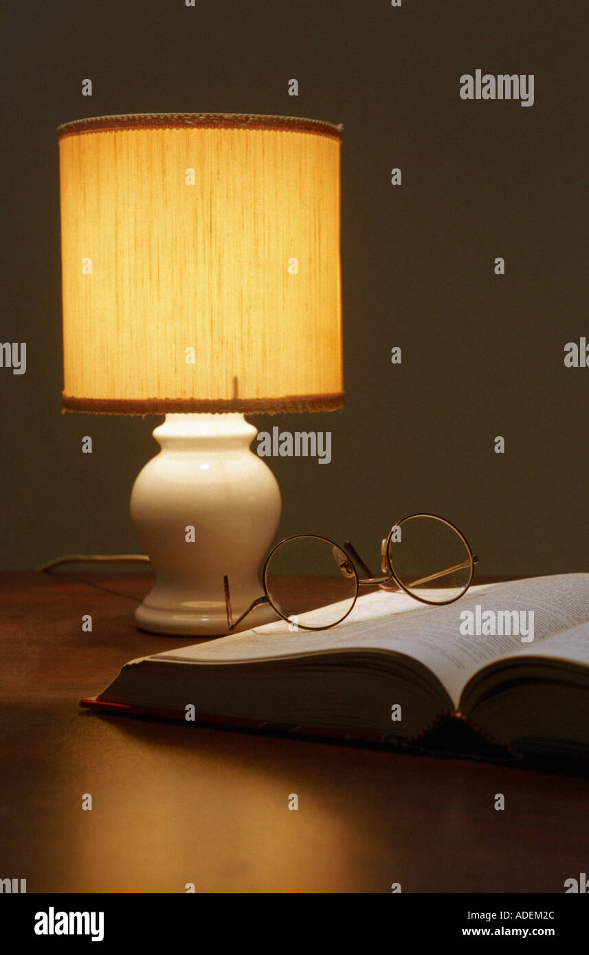 reading lamp with an open book and a pair of glasses - Stock Image