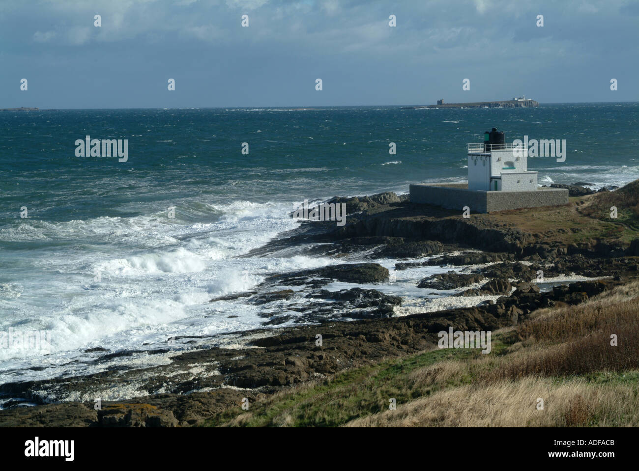 Stag Rock Lighthouse with Rough North Sea and Inner Farne Island Bamburgh Northumberland England United Kingdom Stock Photo