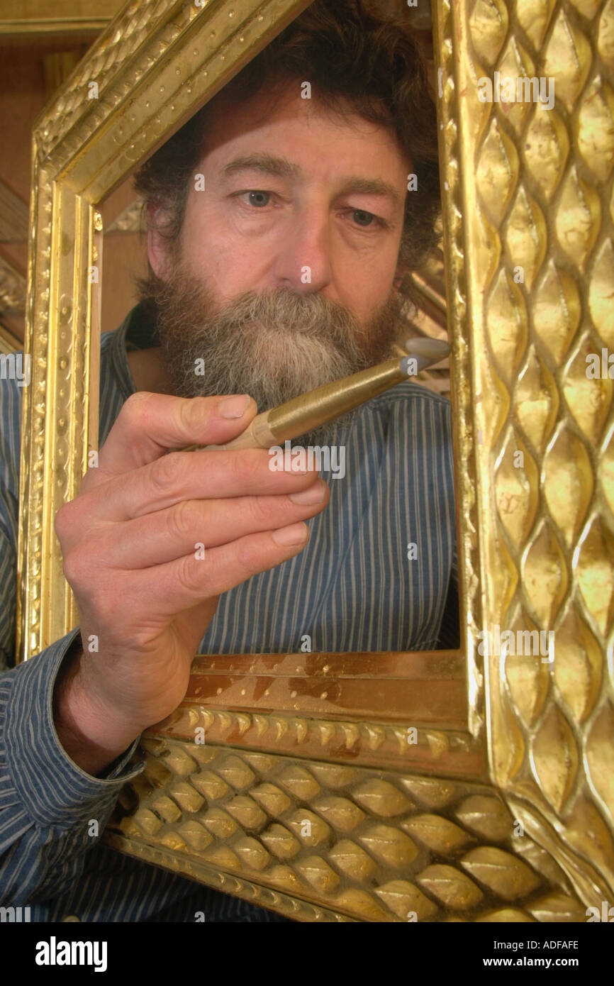 Gilder John Poole burnishing a hand carved bespoke picture frame in gold leaf water gilded England UK - Stock Image