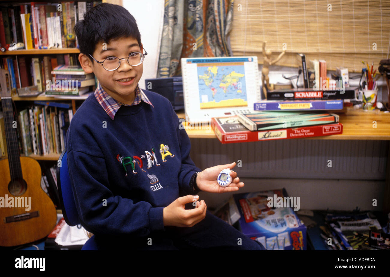 Young boy sitting in his bedroom at his desk holding a tamagotchi computer top with games in background. Stock Photo