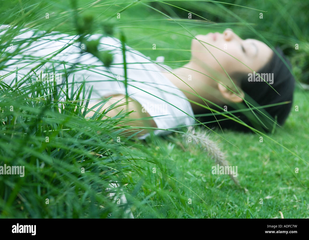 Woman lying on grass, eyes closed, focus on plants in foreground Stock Photo