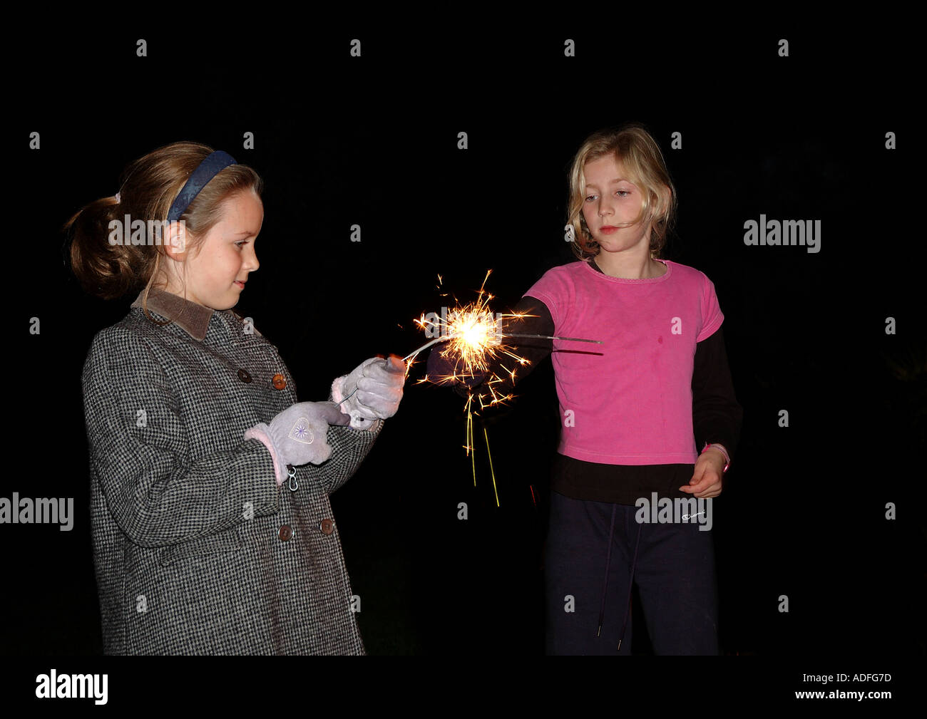 children playing with sparklers on bonfire night - Stock Image