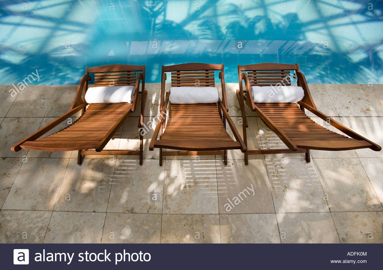 three wooden deck chairs arranged along the edge of a swimming pool - Swimming Pool Deck Chairs