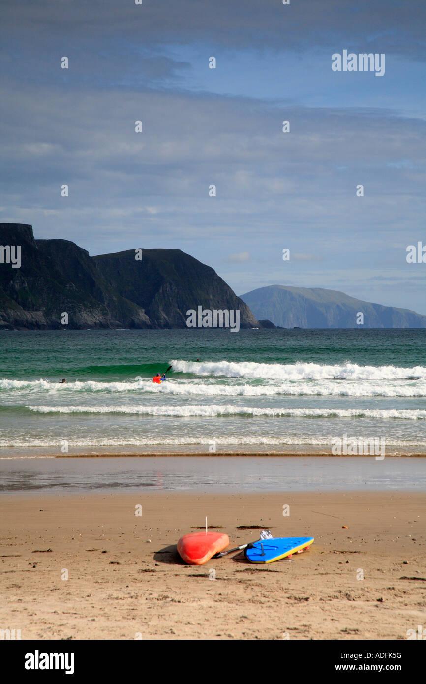 Surfers on Keel beach below Minaun cliffs, Achill Island, County Mayo, Ireland. - Stock Image