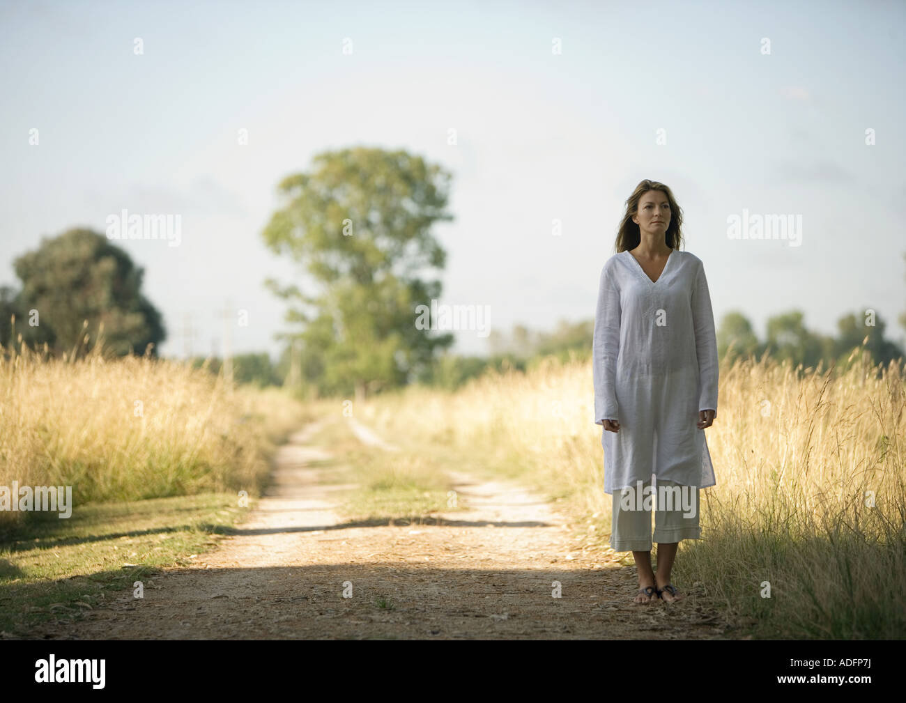 Woman standing on edge of dirt road, next to field - Stock Image