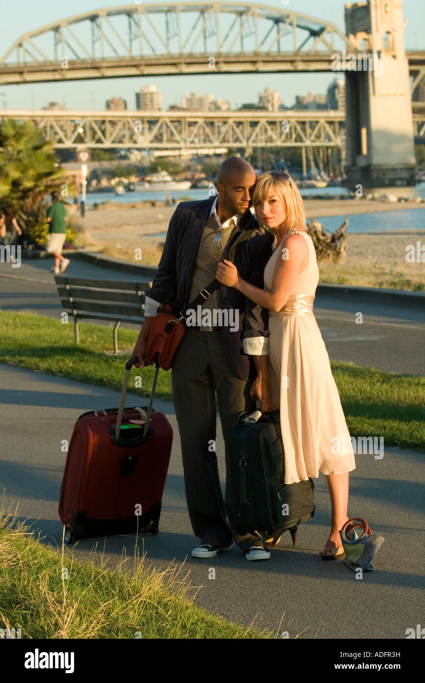 Close-up of a black man and a white woman couple with Vancouver Burrard Street bridge in background. - Stock Image
