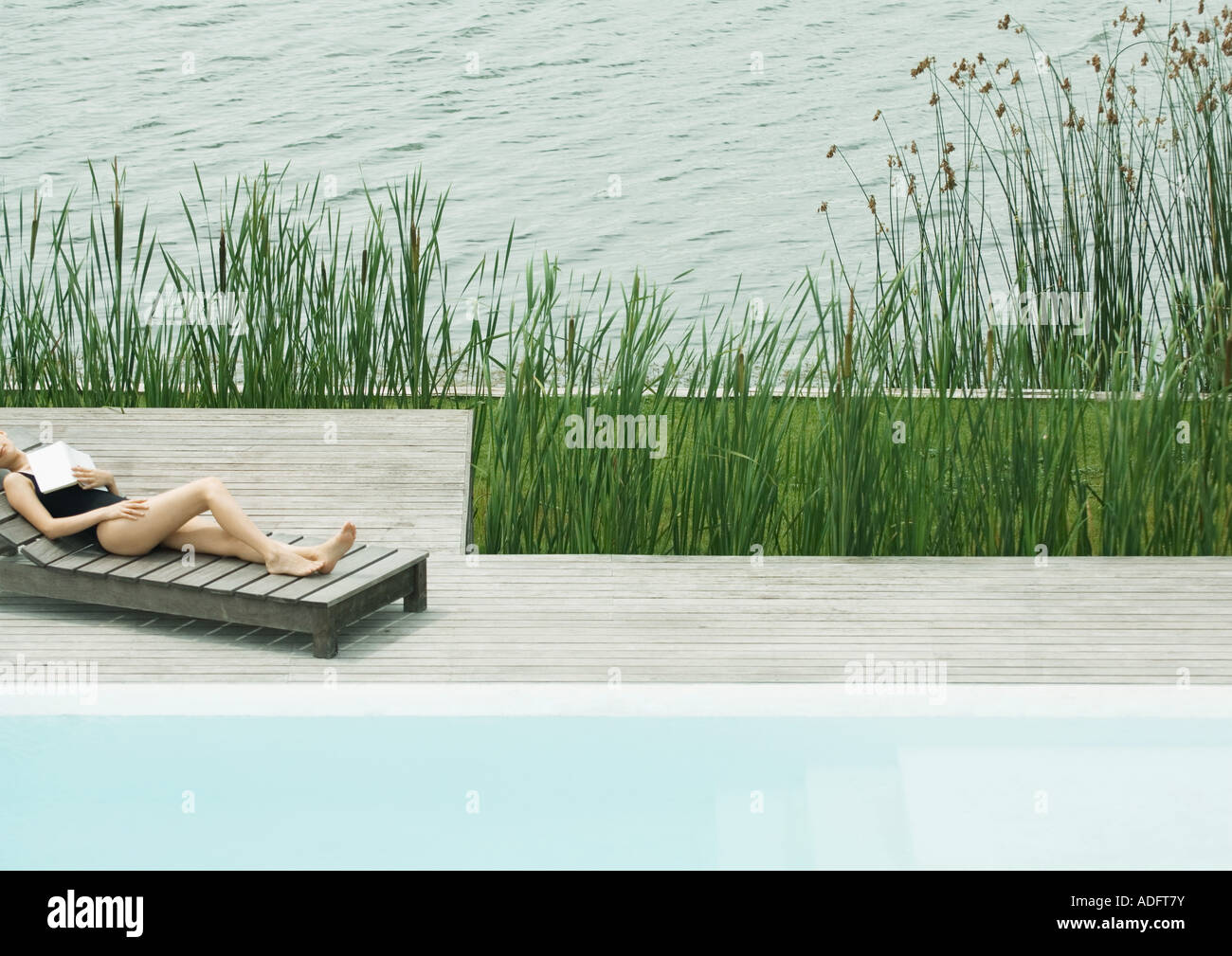 Woman reclining on lounge chair next to lake, sleeping with book on chest - Stock Image