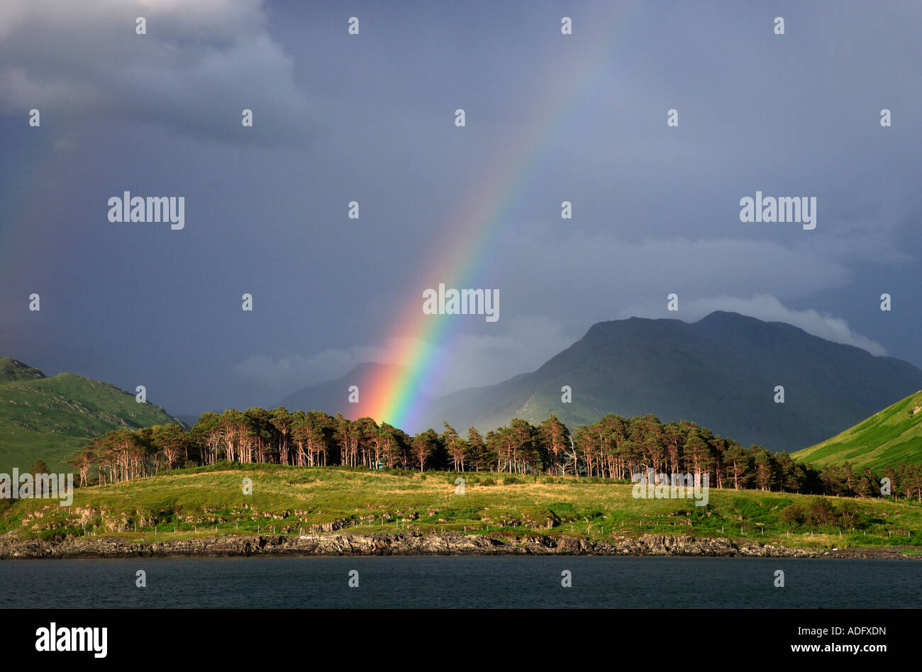 A RAINBOW AND DARK BROODING SKY MAKE A DRAMATIC BACKDROP TO INVERIE KNOYDART. - Stock Image