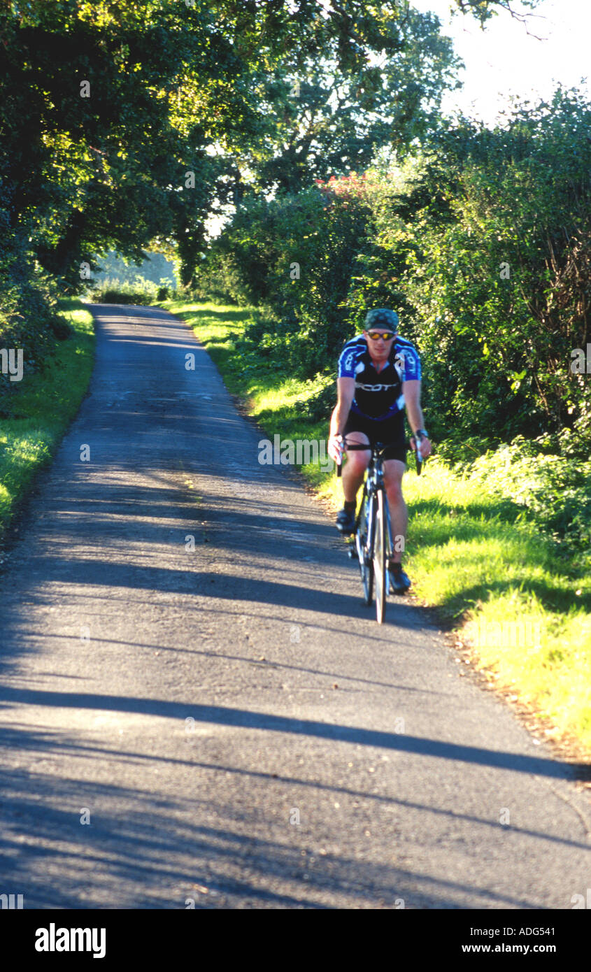 Cyclist on a sunlit country lane Pevensey marshes East Sussex England UK Britain - Stock Image