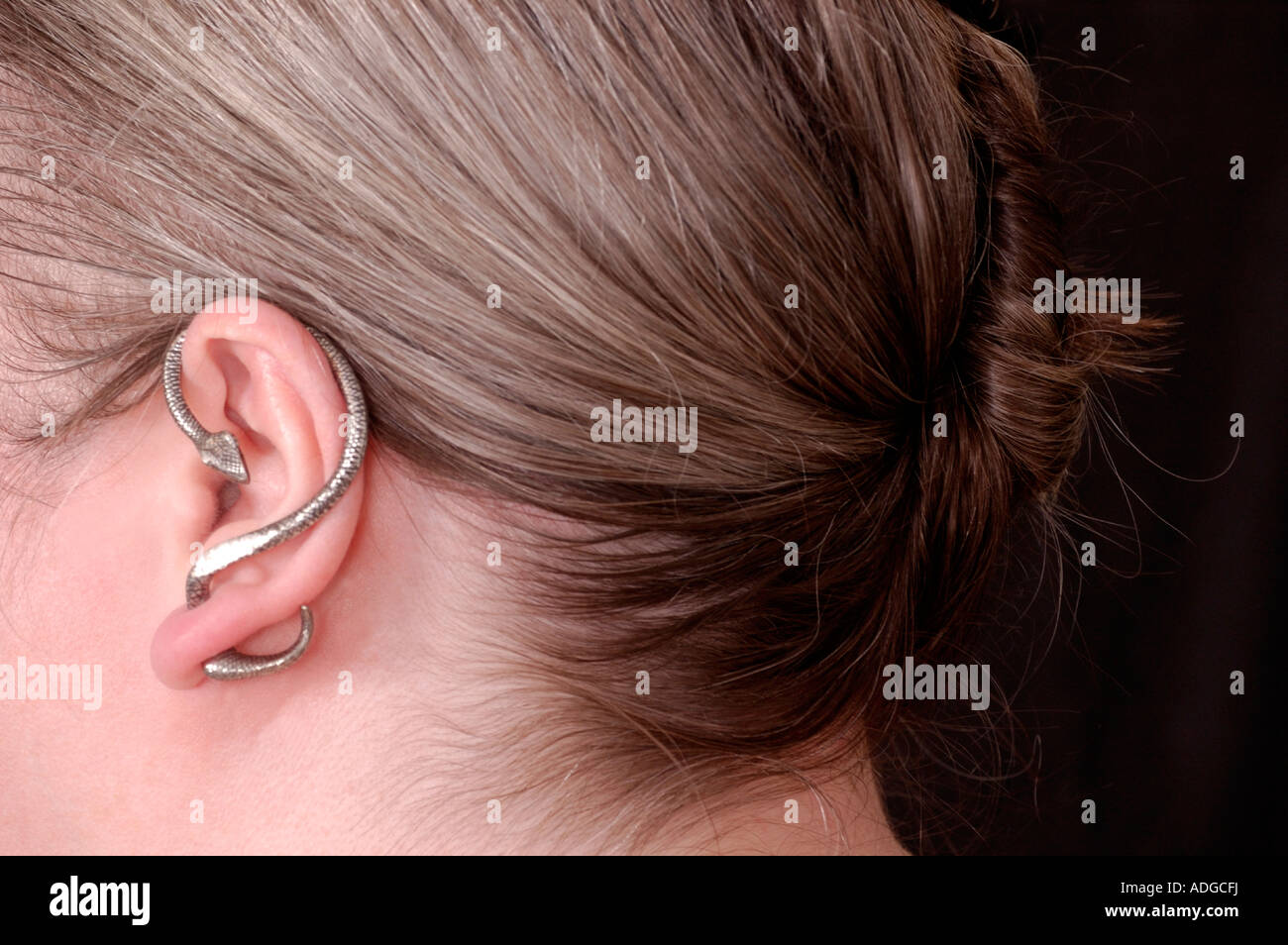 Girl wearing snake earcuff with hair in a french twist - Stock Image