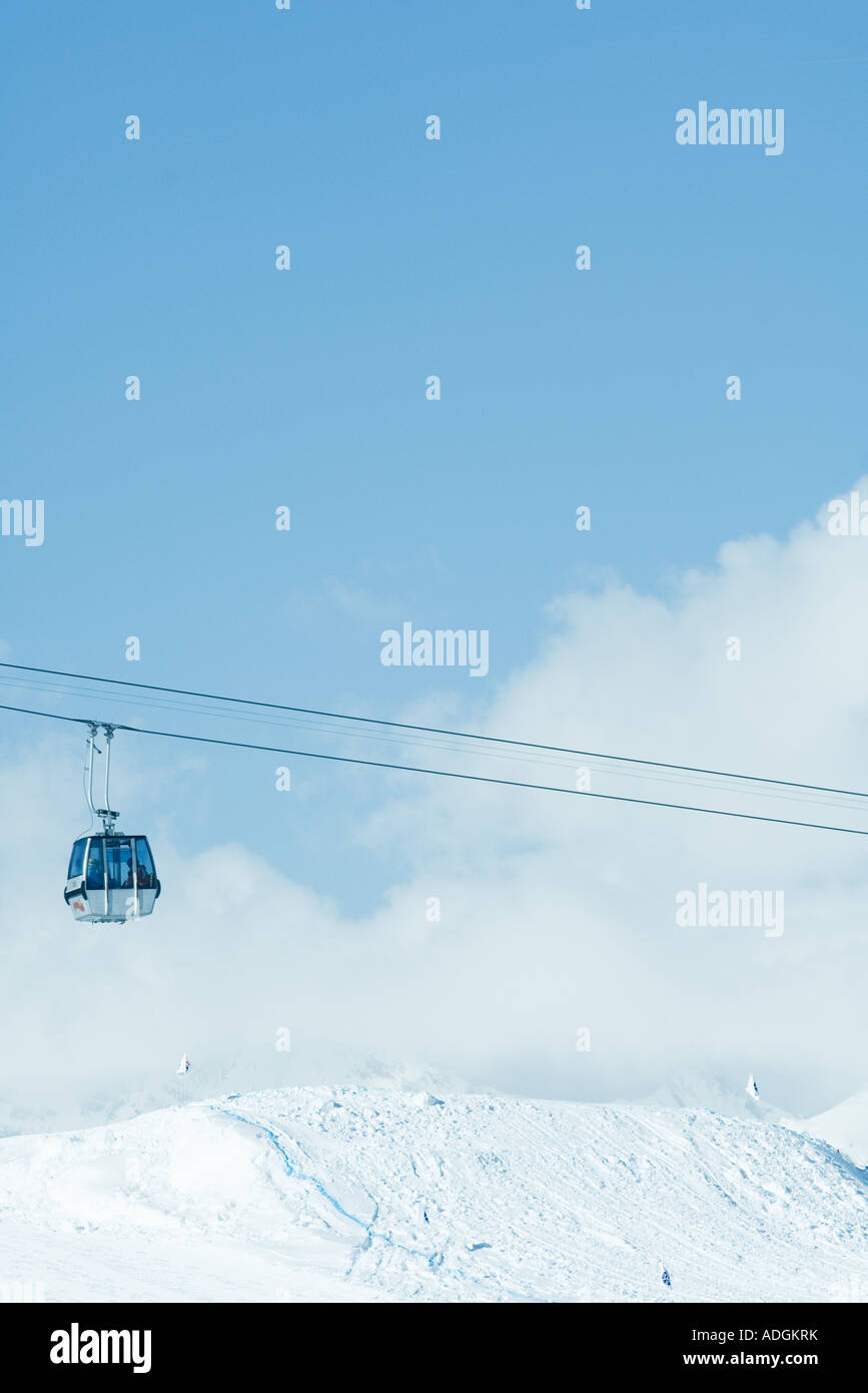 Cable car moving over snow-covered slope - Stock Image