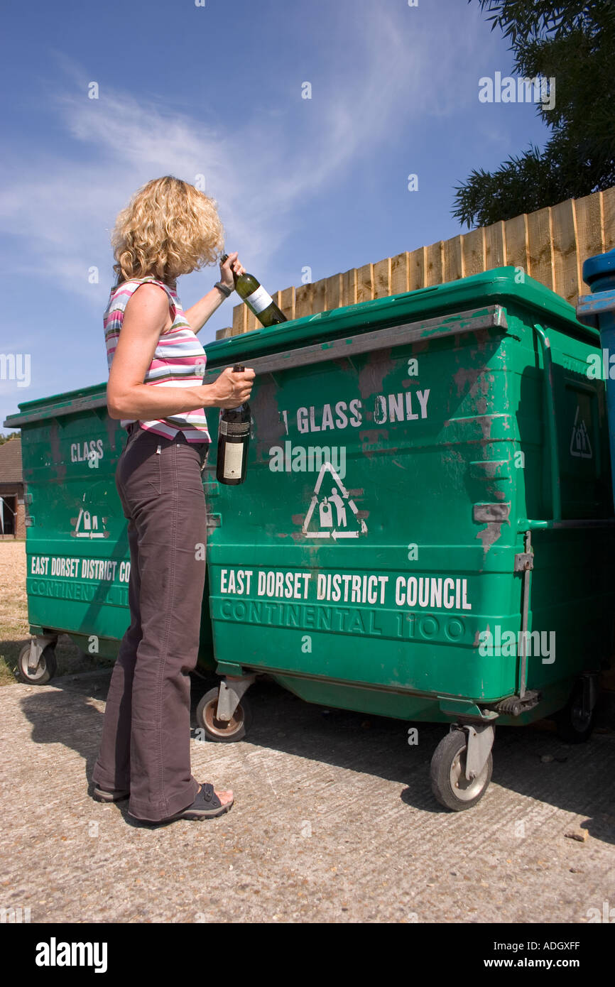 Young woman recycling bottles at bottle bank - Stock Image